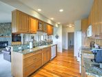 The fully equipped kitchen features hardwood flooring and granite counter tops.