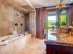 The private bathroom to Master Bedroom #1 features a double vanity, a jetted tub, and a separate walk-in shower.