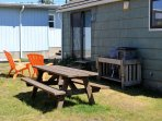 Picnic table and sitting area in backyard with charcoal barbeque