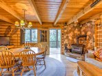 Inside, enter into the open living area with plush seating, a wood-burning stove, and flat-screen TV with DirecTV.