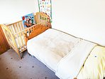 Single bedroom with childs cot / crib.  View 2