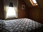Queen bedroom with ocean view and skylight.