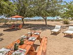 A large picnic table in the yard is perfect for enjoying a meal outdoors.