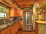 The fully equipped kitchen is a dream with gorgeous counter tops, stainless steel appliances and exposed wood ceiling.