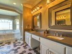 The en suite bathroom offers tiled floors, his-and-hers sinks and a bathtub with a window offering stunning views.