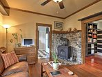 The rustic living room features a plush leather couch, recliner, and wood-burning oven surrounded by beautiful...