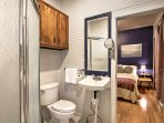 Enter the jack and jill bathroom featuring a walk-in shower and charming shiplap walls.