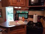 Fully functional kitchen, with a stove, oven, microwave, and a full refrigerator and freezer
