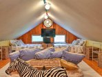 This bunk loft room contains 4 full-sized beds and 1 king-sized bed, providing ample sleeping space.