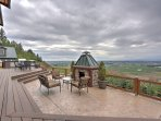 The cliff side deck with a full outdoor kitchen and fireplace offers a cozy and comfortable area to dine, relax, and...