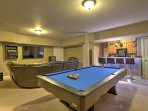 The downstairs game room offers a full kitchen, wet bar, wine cooler, shuffleboard, pool tables, a poker table and a...
