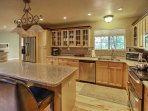 The kitchen space features stainless steel appliances, ample counter space and a breakfast bar.