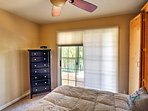 This room contains a queen-sized bed and a sliding door that leads outside.