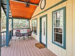 The front porch offers a relaxing spot to sit at the table and enjoy a game of cards with a travel companion.