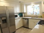 Kitchen equipped with stainless appliances and all cooking utensils.