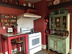 Gas stove, bright serving ware in hutch and spices in rack above table.