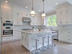 The fully equipped gourmet kitchen is a chef's dream, offering spacious marble counters, a wine refrigerator, 3 ovens...