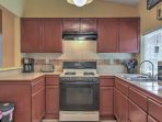 Continue into the fully equipped kitchen with modern appliances and beautiful wood cabinets.