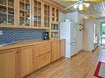 The fully equipped kitchen features a beautiful back splash, and warm wood cabinets.
