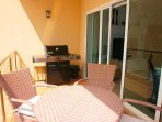 Balcony off the living area with outdoor 4-seat dinning table an BBQ grill