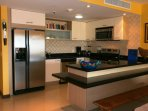A full-sized fully equipped open kitchen with bar