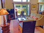 The living room features a flat-screen cable TV, sleeper sofa, and direct access to the furnished lanai.