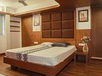 Air-conditioned master bed room with a built-in wardrobe and attached toilet.