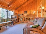 Rustic wood paneling and cathedral ceiling mark the home's inviting interior.