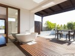 Penthouse bathroom with open air balcony and dining area