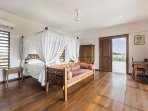 Penthouse bedroom with study desk, king sized bed and door to second balcony