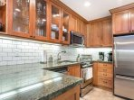 The fully equipped kitchen features granite countertops, stainless steel appliances and plenty of space to cook.