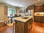 The fully equipped kitchen features stainless steel appliances, granite counter tops and seating at the island for 3.