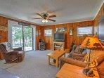 The open living room welcomes you with wood paneling and rustic cabin decor.