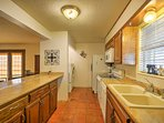 The spacious kitchen features wooden cabinets and beautiful counters.
