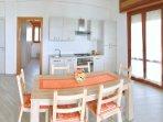 Zona living con cucina, sala da pranzo, TV e angolo lavanderia