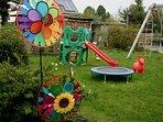 Kinderspielplatz mit Schaukel, Rutsche und Trampolin.