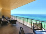 The large balcony over looking the Gulf of Mexico is furnished with comfortable seating and outdoor dining table