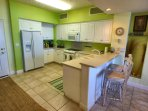 Bright kitchen with nice appliances and bar seating