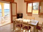 AURORA (1° piano): Zona living con cucina vista mare, sala da pranzo e TV