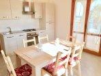 AURORA: Zona living con cucina vista mare, sala da pranzo e TV