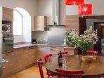 La cuisine rénovée et toute équipée avec sa grande table ovale permettant de loger 12 personnes