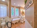 The pristine master bathroom includes a clawfoot soaking tub.