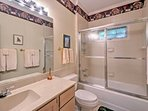 This full bathroom features a mirrored vanity and tub-shower combo.