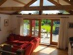 Open plan sitting room with oak terrace doors to Indian stone terrace