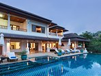 Swimming pool and villa at sunset