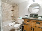 The beautiful bathroom features attractive granite counter tops and a stone tiled tub/shower combo.