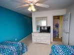 Fourth bedroom with twin beds, direct bathroom access, TV.