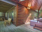 The home features a private deck with outdoor furniture and a hot tub.