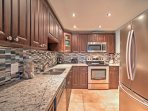 The elegant kitchen features a stunning back splash, stainless steel appliances, and granite counter tops.