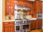 The fully equipped kitchen includes stainless steel appliances, such as this 6-burner gas stove and griddle.
